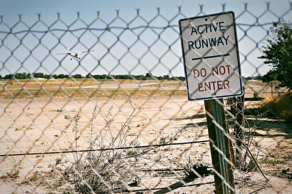 photo of a runway behind a fence