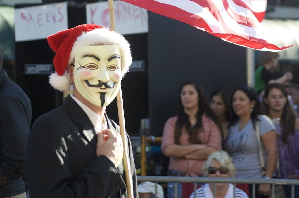 photo of person in Guy Fawkes mask carrying an American flag