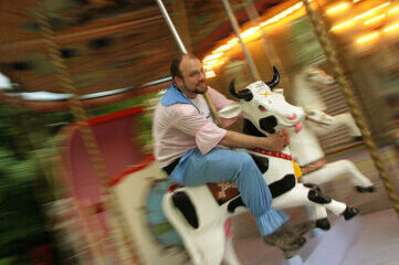 photo of man riding a cow on a merry-go-round