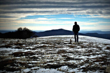 photo of solitary man looking at the mountains on the horizon