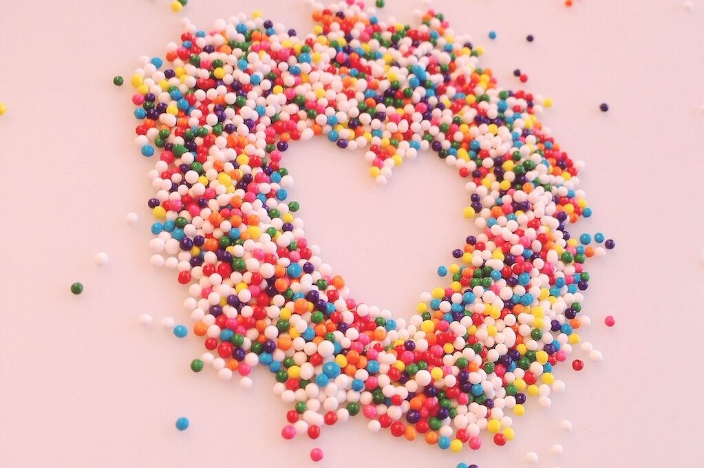 photo of rainbow sprinkles formed into a heart shape