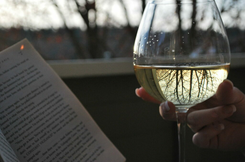 photo of someone holding wine glass and a book