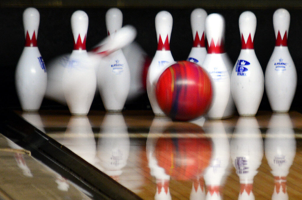 photo of bowling ball striking pins